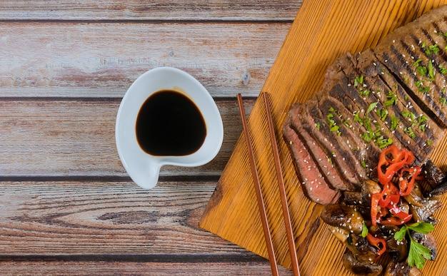 Koreaans gegrild rundvlees en champignons, sojasaus, aan boord met stokjes.