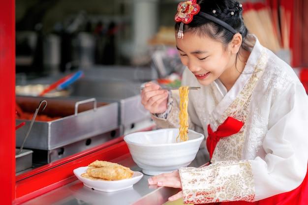 Koreaans meisje eet een noedel met koreaanse traditionele kleding in oud en uitstekend restaurant