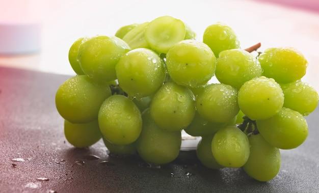 Koreaanse druif met groene schil en waterdruppels rond op de achtergrond, wazig licht rond