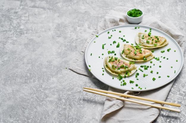 Koreaanse gefrituurde dumplings, eetstokjes, verse groene uien.