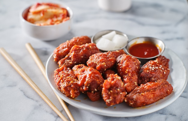 Koreaanse kippenvleugels in gochujangsaus met kimchi en ingelegde radijs