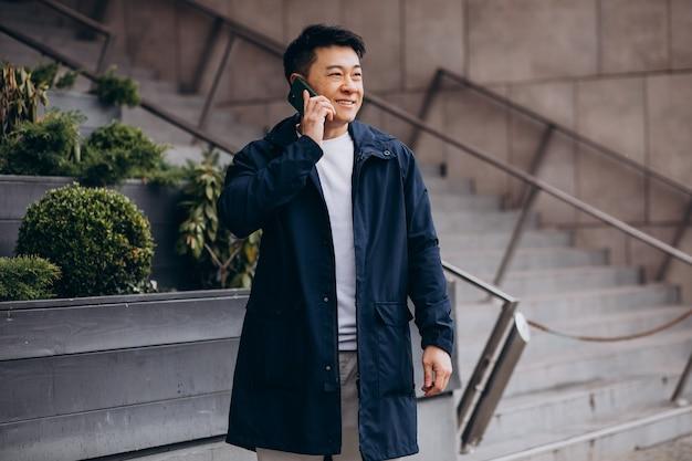 Koreaanse man met telefoon buiten deze boom