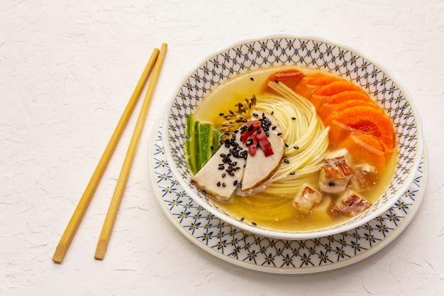 Koreaanse noedelsoep met gerookte kip en groenten. pittig gerecht voor een gezonde maaltijd