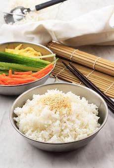 Koreaanse rijst met wit sesamzaad bovenop, achtergrondkomkommer, ei en wortelen. ingredoent bereidingsproces gimbap of kimbap, korean roll rice maken