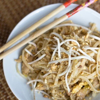 Koreaanse rijstnoedels met sojascheuten en gemalen pinda's in een witte kom met stokjes