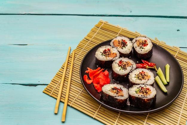 Koreaanse rol gimbap (kimbob). gestoomde witte rijst (bap) en diverse andere ingrediënten. trendy turquoise achtergrond