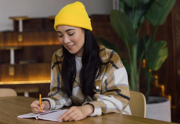 Koreaanse student studeert, leert taal, examenvoorbereiding bij moderne bibliotheek, onderwijsconcept. aziatische vrouw planning opstarten project, het maken van aantekeningen, werken op kantoor. succesvol bedrijfsconcept