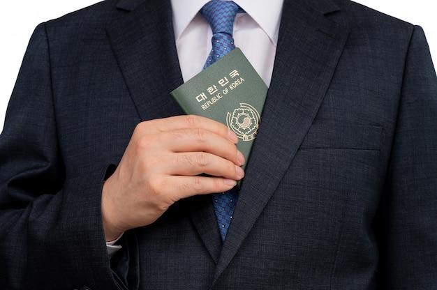 Koreaanse zakenman die een koreaans paspoort in hand houdt.