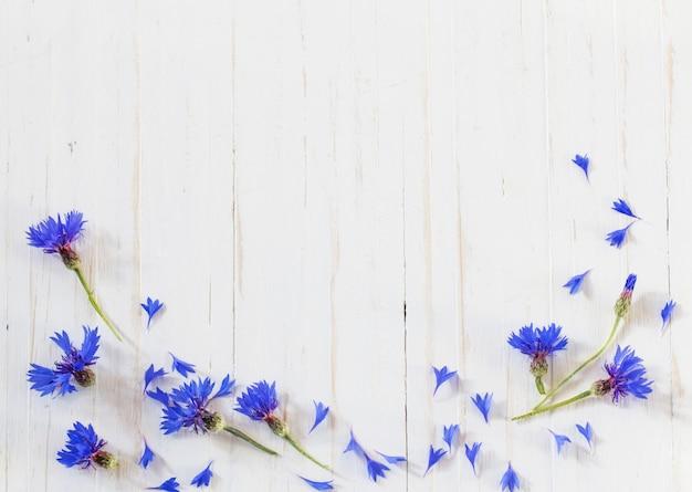Korenbloemen op witte houten achtergrond