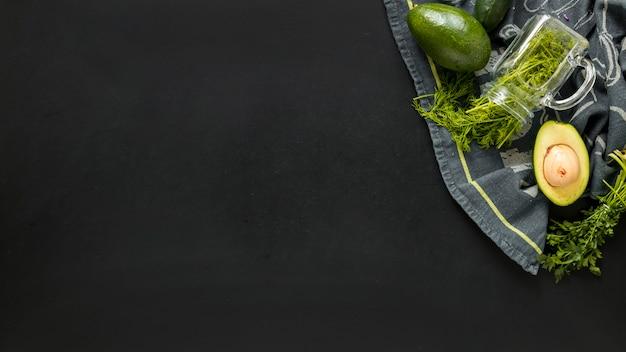 Koriander en gehalveerde avocado op tabletdoek tegen zwarte achtergrond