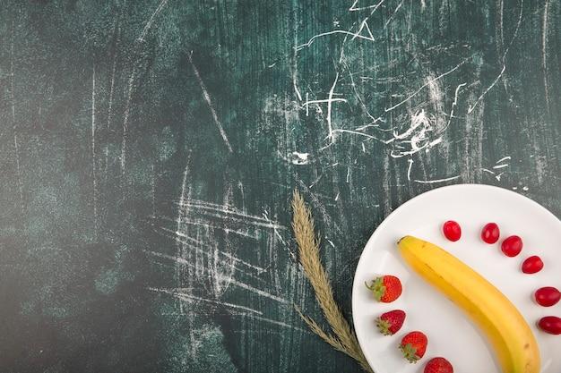 Kornoelje, aardbeien en banaan in een wit bord in de benedenhoek