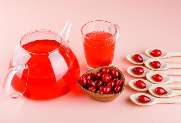 Kornoelje bessen in houten lepels en kom met hoge hoekmening van dranken op roze