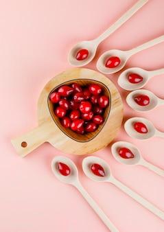 Kornoelje bessen in houten lepels en kom op roze en snijplank, bovenaanzicht.