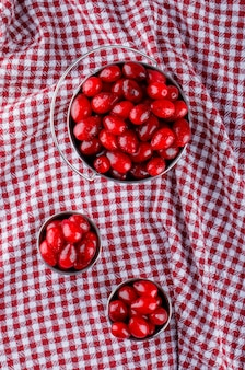 Kornoelje bessen in mini emmers op picknickdoek. bovenaanzicht.