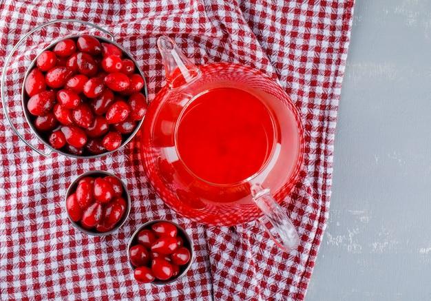 Kornoelje bessen met drank in mini emmers op gips en picknickdoek.