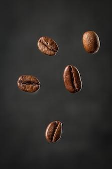 Korrels van geroosterde koffie die op grijze achtergrond vallen