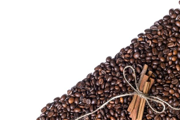 Korrels van koffie en kaneel op een witte achtergrond. bovenaanzicht. stilleven. ruimte kopiëren. plat leggen.