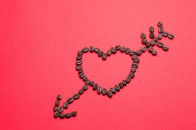 Korrels van koffie in de vorm van een hart op een rode achtergrond