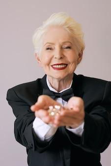 Kort haar stijlvolle senior vrouw in smoking met glitter nieuwjaar vieren