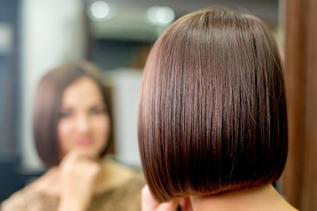 Kort kapsel van een vrouw terwijl ze in de spiegel kijkt naar de kapsalon.