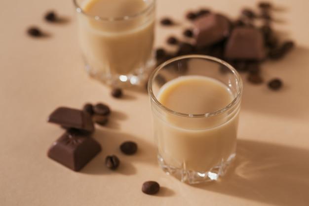 Korte glaasjes irish cream liquor of coffee likeur met chocolade en koffiebonen. kerstdecoraties voor de winter