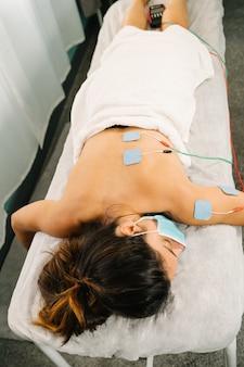 Korte opname van een blanke vrouw die een fysiotherapiebehandeling krijgt met elektrostimulatie-elektroden op haar rug terwijl ze op een brancard ligt met een gezichtsmasker vanwege de coronaviruspandemie van covid 19.