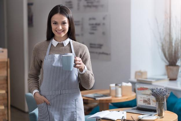 Korte rust. charmante mooie vrouw glimlachend en staande in een café terwijl ze een kopje thee vasthoudt.