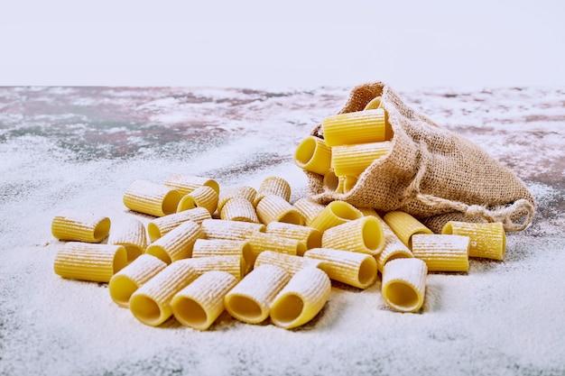 Kortgesneden pasta in een zak op houten tafel.