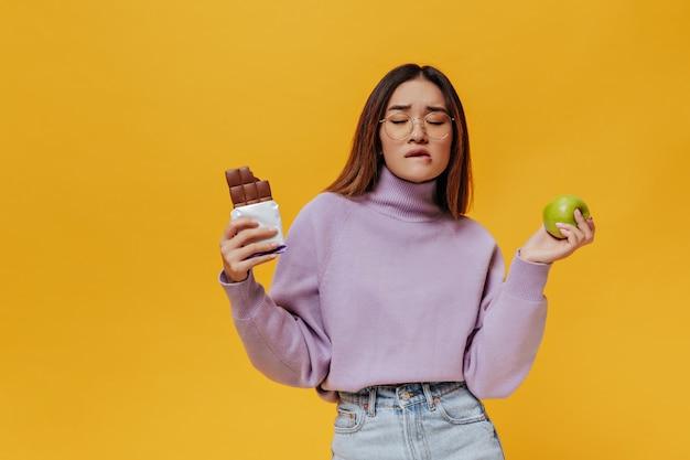 Kortharige aziatische vrouw in bril, paarse trui en spijkerrok merkt haar lip op en probeert te beslissen wat ze moet kiezen: verse groene appel of smakelijke zoete chocoladereep