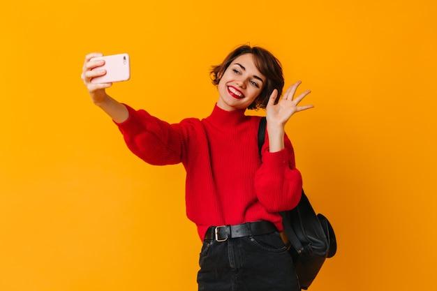 Kortharige blanke vrouw zwaaiende hand op gele muur