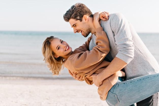 Kortharige blonde dame omhelst echtgenoot in het strand. outdoor portret van goedgehumeurde man dansen met vriendin in de buurt van de oceaan.