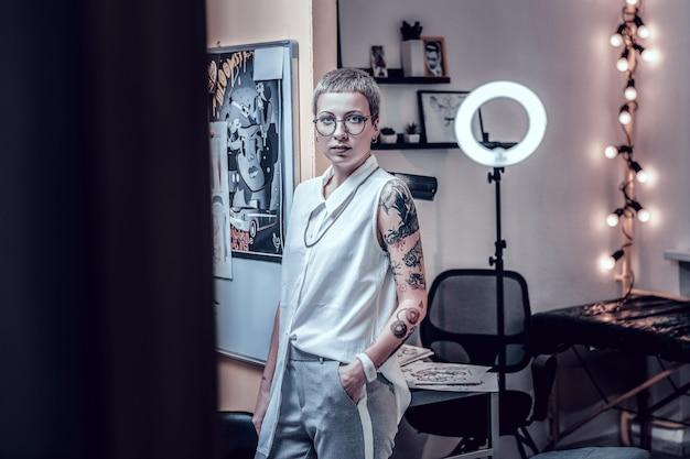Kortharige buitengewone vrouw. aantrekkelijke vrouw met een ongewoon uiterlijk die werkt als tattoo-meester die mouwloos wit overhemd draagt