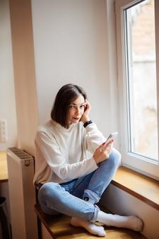 Kortharige dame die in jeans op de vensterbank zitten en bericht op smartphone thuis schrijven