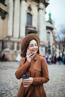 Kortharige dame in lichte hoed praten over phote en sms-berichten op haar telefoon