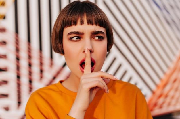 Kortharige dame in oranje modern sweatshirt die naar buiten kijkt Gratis Foto