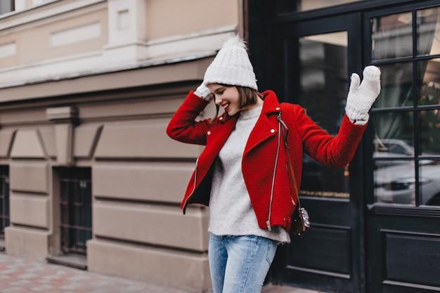 Kortharige dame in witte hoed en wanten lacht. portret van meisje met rode lippenstift gekleed in licht jasje en spijkerbroek op achtergrond van etalage.