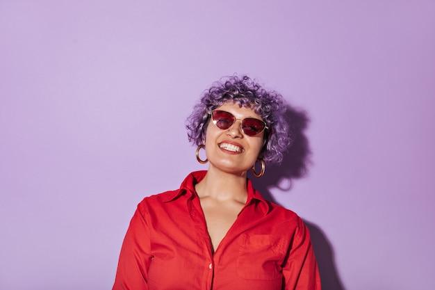 Kortharige krullende vrouw met stijlvolle heldere bril, in rood shirt met lange mouw en glimlacht op geïsoleerde lila.