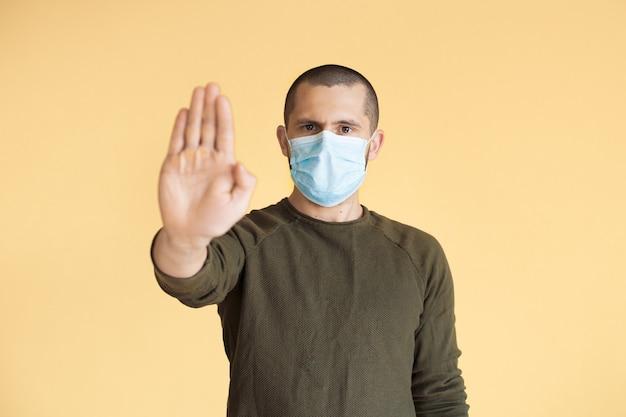 Kortharige man gebaart het stopbord met palm poseren op een gele muur met een medisch masker
