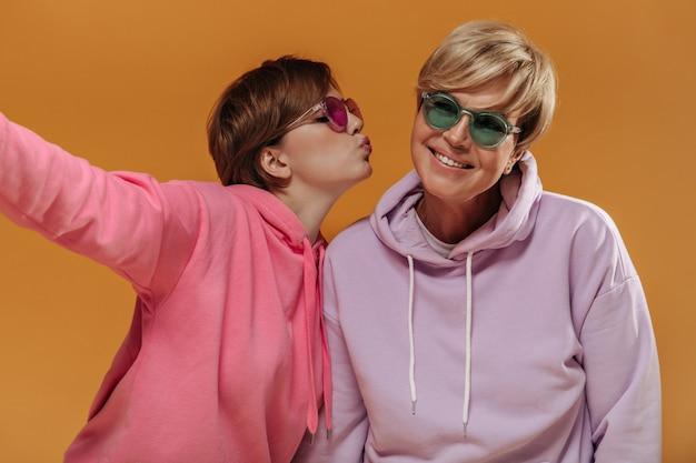 Kortharige meisje in roze hoodie zoenen op wang en selfie maken met blonde dame in groene zonnebril op oranje achtergrond.