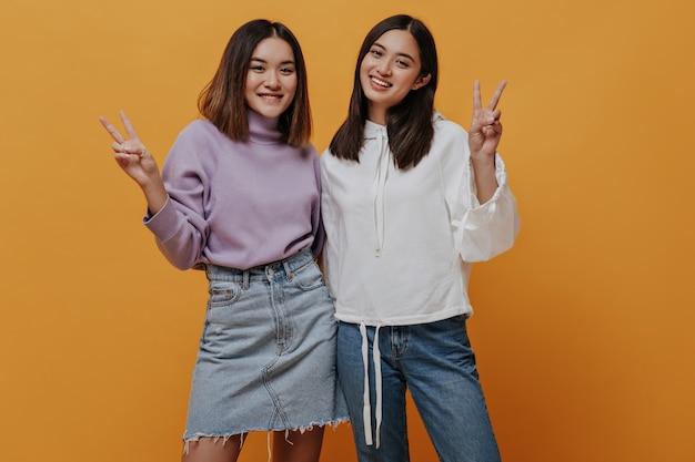 Kortharige meisjes vertonen v-tekens en glimlachen op geïsoleerde
