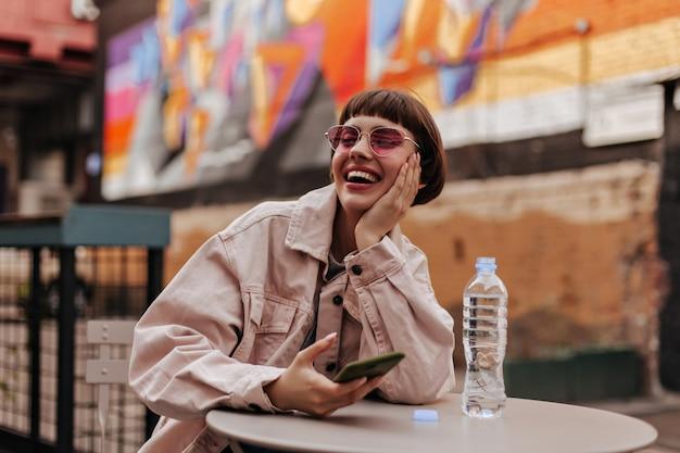 Kortharige tiener met heldere bril en lichte kleding die telefoon vasthoudt en lacht om straat