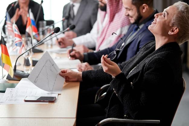Kortharige uitvoerende vrouw is in shock na wat ze in het document zag, ze gooide haar hoofd achterover en lachte, tijdens een vergadering in de directiekamer