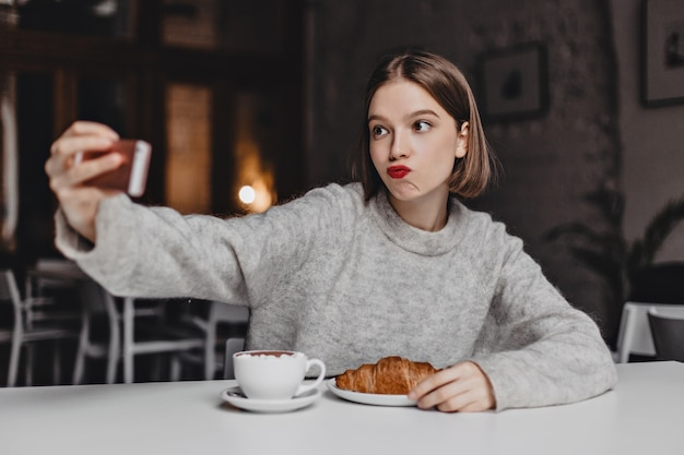 Kortharige vrouw in kasjmier sweatshirt bestelde croissant en cappuccino in café en neemt selfie.