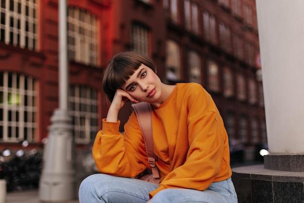 Kortharige vrouw in oranje trui zit buiten