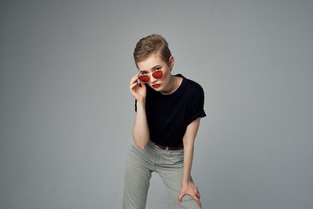 Kortharige vrouw met zonnebril mode geïsoleerde achtergrond