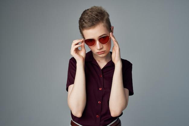 Kortharige vrouw met zonnebril mode lichte achtergrond. hoge kwaliteit foto