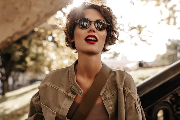 Kortharige vrouw met zwarte zonnebril in olijfjasje kijkt weg naar buiten. prachtige vrouw met felle lippenstift buitenshuis poseren.