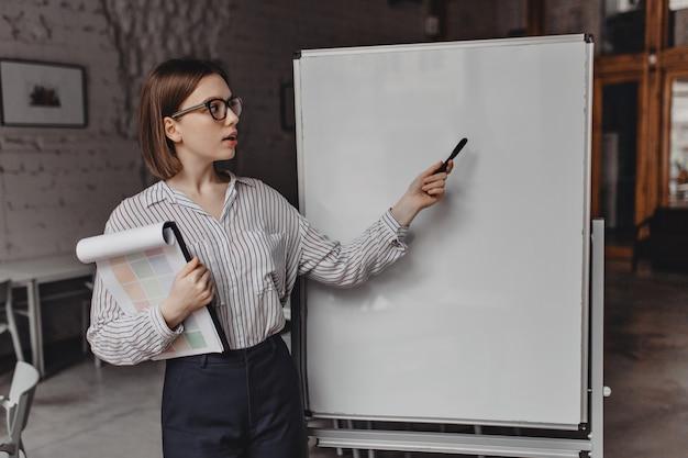 Kortharige werknemer in witte blouse en zwarte broek shows op kantoor bord. portret van een vrouw met documenten die over plannen vertellen.