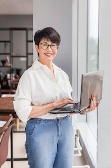 Kortharige zakenvrouw met behulp van laptop en glimlacht