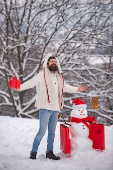 Korting en winter verkoop concept. grappige sneeuwpop met boodschappentas - korting en winter verkoop concept